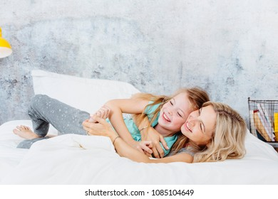 Beautiful Mother and daughter cuddle up in bed