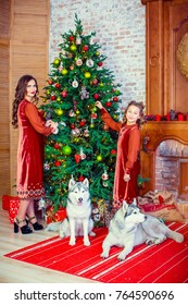 A beautiful mother and daughter decorate the New Year tree. Celebrating the New Year, Christmas.