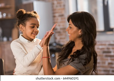 Beautiful mother and daughter giving high five and smiling each other