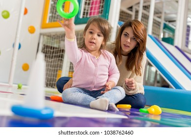 Beautiful mother and daughter having fun playing in a playroom. Focus on the mother
