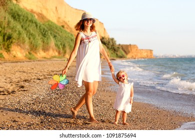 Beautiful mother and daughter having fun walking and playing on the beach at sunset. Family, vacation concept.