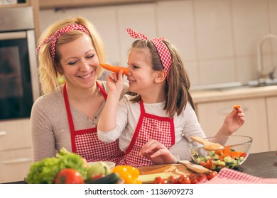 Beautiful mother and daughter having fun in the kitchen while cutting vegetables for salad; daughter making carrot nose. Focus on the daughter