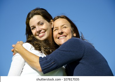 Beautiful mother and daughter hugging each other on a sunny  day outside, with clear blue sky as background and copy space.