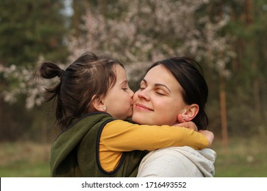 Beautiful mother and daughter hugging and kissing in casual clothes. Warm baby hug on the background of a blurry flowering tree