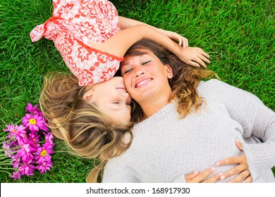Beautiful mother and daughter lying together outside on grass, Happy intimate moment, Cute little girl snuggling her mom