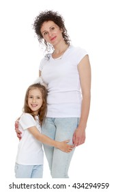 Beautiful mother and daughter in matching jeans and white shirts.Girl hugging mom's legs - Isolated on white background