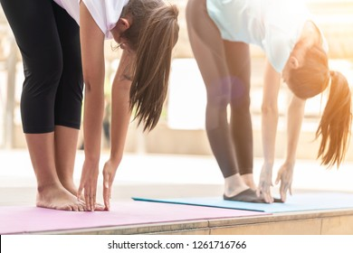 beautiful Mother and Daughter or Mature woman and teenage girl exercising in the city. Two friends female fitness model doing yoga or stretching her working out in the morning. Good Health,Warm Tone