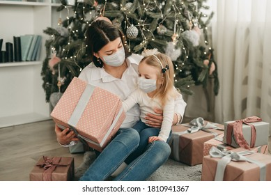 Beautiful mother and daughter in medical masks have fun at home near the Christmas tree in a white interior. Family happiness, holiday, joy, vacation, games with a woman. New Year's preparations. Cele