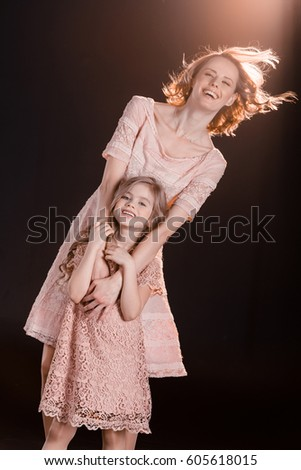 af5f22f0d9 Beautiful mother and daughter in pink dresses hugging and smiling at camera  isolated on black