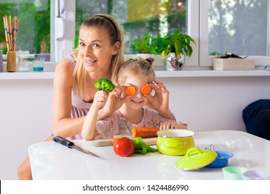 Beautiful mother and daughter playing while preparing dinner,happy and healthy life concept