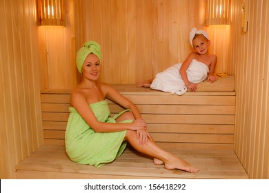 beautiful mother and daughter in the sauna. smiling and looking into the frame.