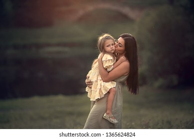 Beautiful mother and daughter are walking in the park, hugging and having fun. Image with selective focus and toning.