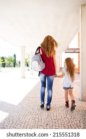Beautiful mother and daughter walking to school