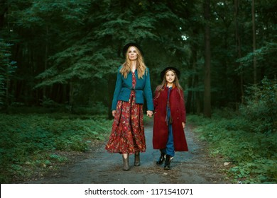 Beautiful mother and daughter are walking through the forest. They hold hands.
