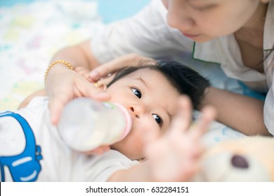 beautiful mother feeding baby boy with a milk bottle at home