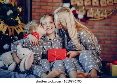Beautiful mother in a gray pajamas. Family sitting on a bed. Little girl and boy near christmas tree
