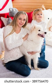 Beautiful mother with a happy daughter in a New Year's interior with a white fluffy dog, Samoyed Laika
