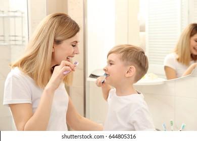 Beautiful mother and happy son brushing teeth near mirror in bathroom