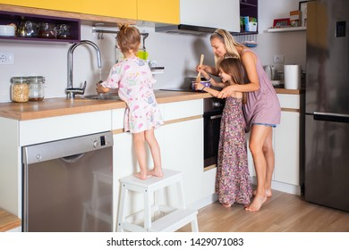 Beautiful mother helping older daughter while she cooking,learning her and giving advice. Younger daughter  washing dishes.Family life concept