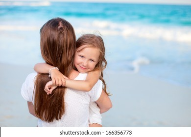 Beautiful mother and her adorable little daughter at beach
