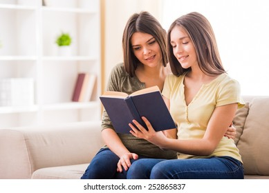 Beautiful mother and her cute teen daughter are reading a book together while sitting on sofa at home.
