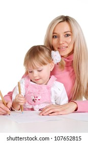 A beautiful mother with her daughter paint crayons on a white background