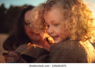 Beautiful mother and her little daughter are having fun together on the lake Ladoga in Russia during the sunset. Image with selective focus, noise effects and toning.