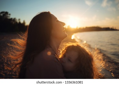 Beautiful mother and her little daughter are having fun together on the lake Ladoga in Russia during the sunset. Blurred image with toning.