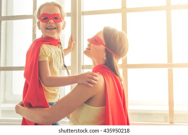 Beautiful mother and her little daughter dressed like superheroes are smiling while playing at home