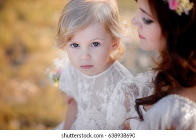 Beautiful mother with her little daughter in amazing dresses, outdoors