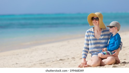 beautiful mother and her little son sitting together at the beach, vacation together