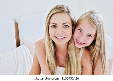 Beautiful mother and her pretty daughter teenager smiling at home