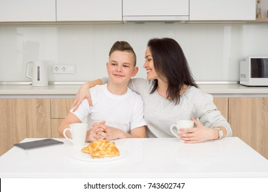 Beautiful mother with her son having sitting at table in kitchen and having conversation, smiling and hugging. Family concept about good communication and connection