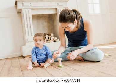 Beautiful mother and her son playing with wooden toys at home