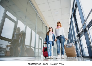 Beautiful mother and her stylish cute daughter walk together and pull a pink suitcase at airport. High season and vacation concept. Relax and lifestyles