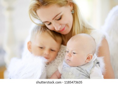 Beautiful mother with her toddler and newborn sons wearing angel costumes. Cheerful moment, loving family. Mom is the Guardian angel for her child concept