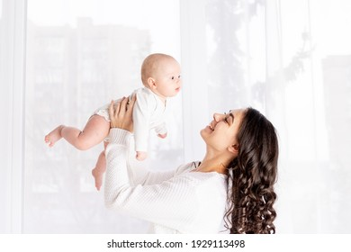 beautiful mother holding a baby in her arms at the window of the house, the concept of a happy loving family, lifestyle