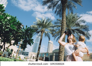 Beautiful mother holding cute little daughter and looking through binoculars in Dubai, UAE