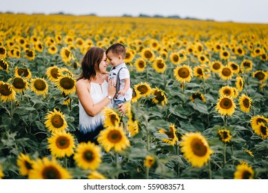 beautiful mother holds a baby son in a sunflower field. tenderness, smiles, happiness