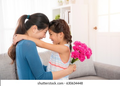 beautiful mother hug with cute little daughter and look each other holding pink bouquet in living room to celebrate the mother's day at home on sofa.