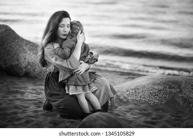 Beautiful mother is hugging and comforting her little daughter on the shore of lake Ladoga in Russia. Black and white image with selective focus, noise effects and toning.