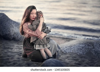 Beautiful mother is hugging and comforting her little daughter on the shore of lake Ladoga in Russia. Image with selective focus, noise effects and toning.