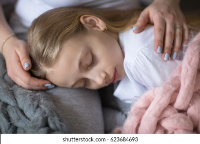 A beautiful mother hugs and gently strokes the daughter of a teenager, mom and daughter with long blond hair, the concept of tenderness and mutual understanding