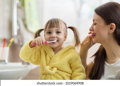 Beautiful mother and kid daughter brushing teeth in bathroom