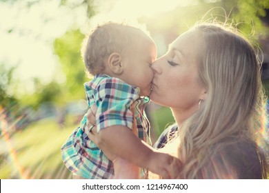 Beautiful Mother kissing her adorable baby boy in the sunset sunlight. Sun rays shining through as the mom shows love to her son