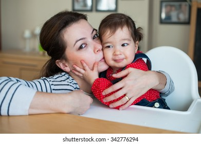 beautiful mother kissing her eighteen month daughter.