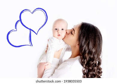 beautiful mother kissing newborn baby holding in his arms a home, the concept of happy loving family, lifestyle