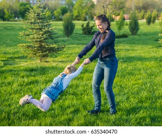 Beautiful mother lifts high her cheerful girl and begins turning her around. They are smiling. Happy family time playing with daughter in park.