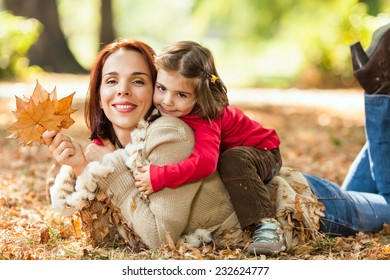 Beautiful mother and little daughter enjoying nice autumn day in a park