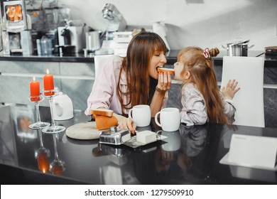 Beautiful mother with little daughter. Family sitting in the kitchen. Cute gitl eat bread